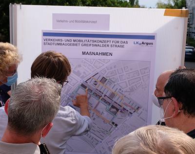 Bürgerinnen und Bürger vor einer Schautafel im begrünten Straßenbereich einer Wohnanlage