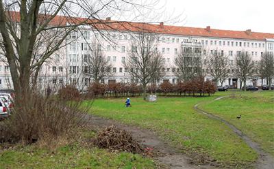 Foto mit Ansicht von Wohnhäusern hinter einer Grünanlage